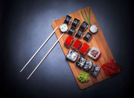 set of sushi rolls on a wooden board with chopsticks