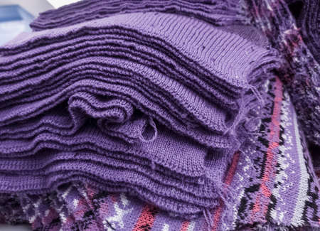 wool lilac knitted parts are placed in a stack for further processing Фото со стока
