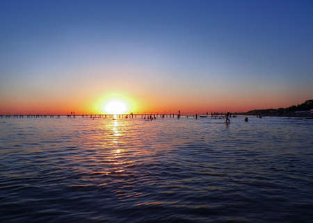 sunset on the sea, a resort town with a pier, silhouettes of vacationing people on the sea Imagens