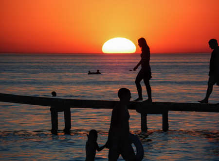 orange sunset on the sea with silhouettes of vacationing people on the pier Imagens