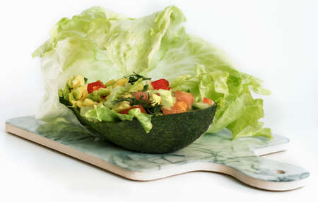 avocado tomato salad with cucumber and green iceberg lettuce served in avocado on the background of green iceberg lettuce 免版税图像