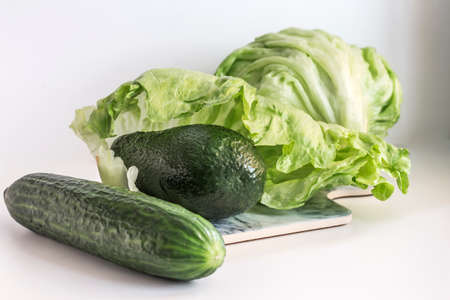 avocado with cucumber on the background of iceberg lettuce, all vegetables are green