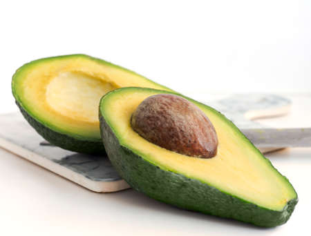 Avocado cut in half, on a white background