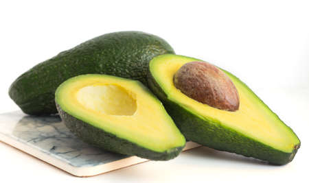 whole green avocado and avocado halves on white background