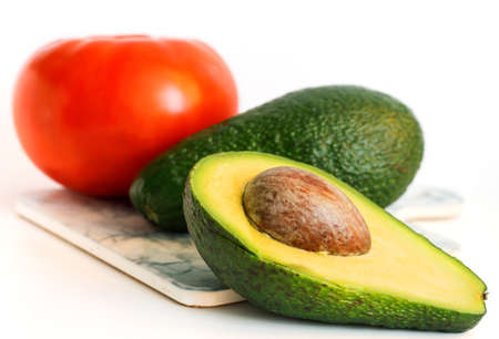 whole green avocado and half avocado with red tomato