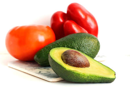 green avocado with red tomato and sweet pepper on a white background