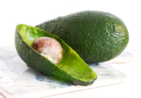 green avocado on a white background with the skin and core of the eaten avocado 免版税图像