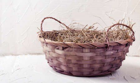 beautiful wicker basket with hay on a white textured background 免版税图像