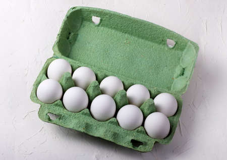 white chicken eggs in a green cardboard box, on a white textured background top view 免版税图像