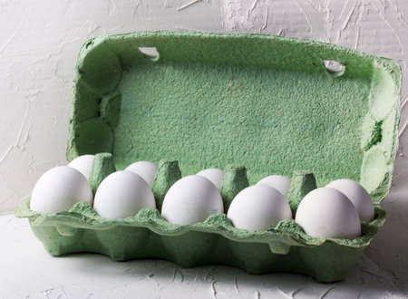 white chicken eggs in a green cardboard box, on a white textured background