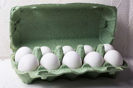 white chicken eggs in a green cardboard box, on a white textured background with a shadow 免版税图像
