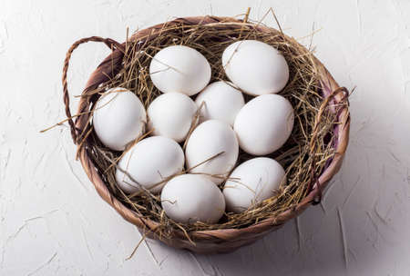 ten chicken white eggs in a basket with hay on a white background 免版税图像