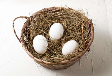 three white chicken eggs in a hay nest on a white background
