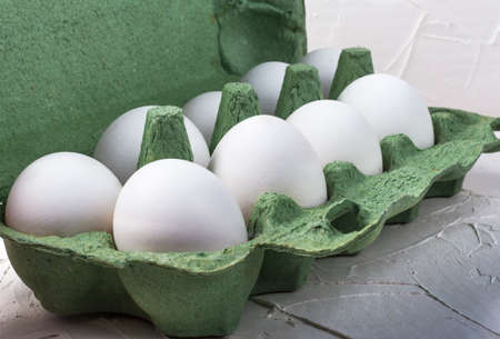 white chicken eggs in a green cardboard container close up on a white background