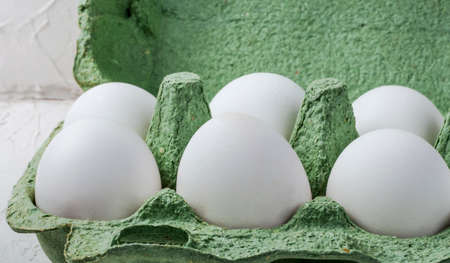 white chicken eggs in a green container close up on a white background 免版税图像
