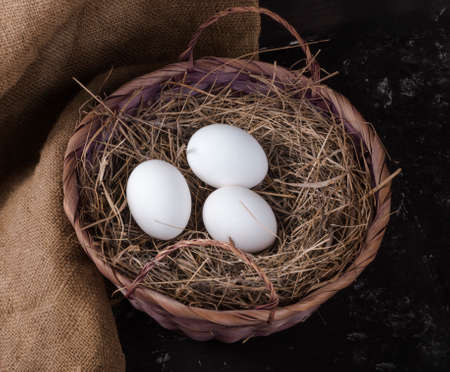 three chicken eggs in a hay basket on a rustic background 免版税图像