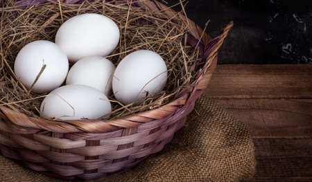 basket of white chicken eggs with hay on a rustic background, with a copy of the space