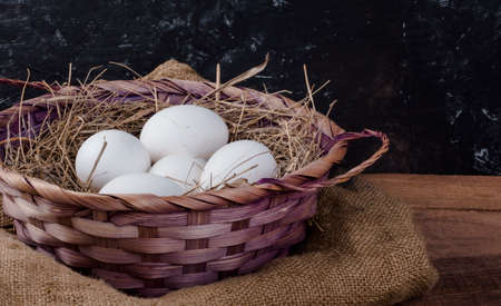 a basket of white chicken eggs with hay on a rustic background