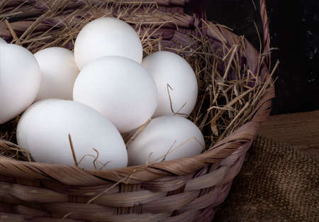 a full basket of chicken eggs with hay on a rustic background, close-up