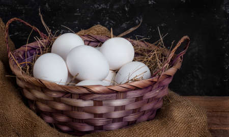 a full basket of chicken eggs with hay on a rustic background 免版税图像