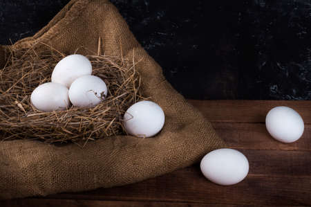 a nest with white eggs and eggs are dropped out of the nest 免版税图像