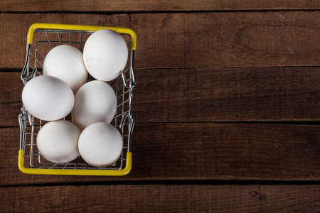 White eggs in an iron food basket on a wooden table, top view, with a copy of the space 免版税图像