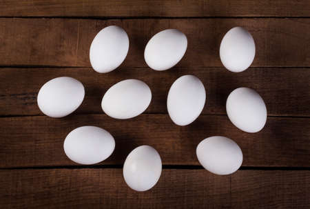 ten white eggs on a wooden rustic background top view 免版税图像