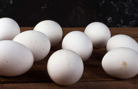 lots of white eggs on a wooden brown background, close-up