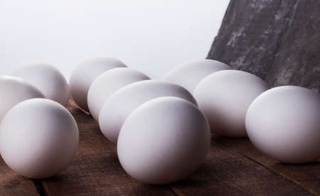 lots of white eggs on a wooden table on a white background, close-up 免版税图像