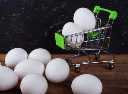 chicken white eggs on the table and in the shopping basket on a black background with a copy of the space