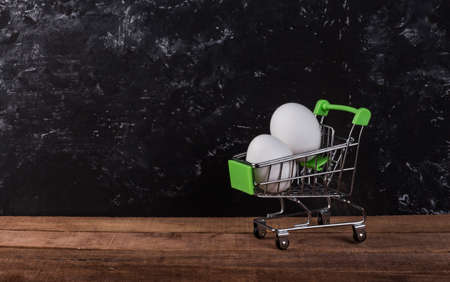chicken white eggs in a shopping basket on a black background with a copy of the space