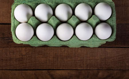 chicken white eggs in a green container on a brown wooden table,top view with a copy of the space 免版税图像