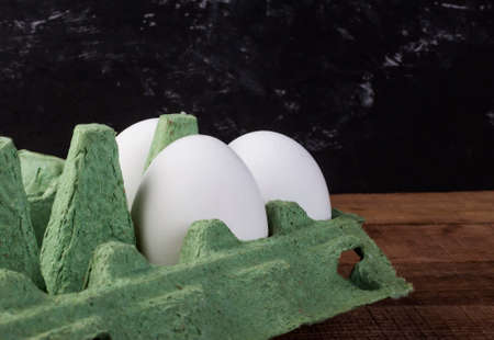 three white chicken eggs in a green container on a brown wooden table 免版税图像