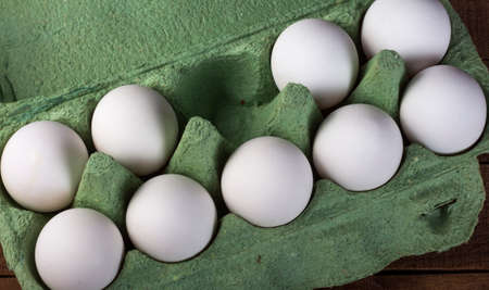 nine white chicken eggs in a green container on a brown wooden table, top view