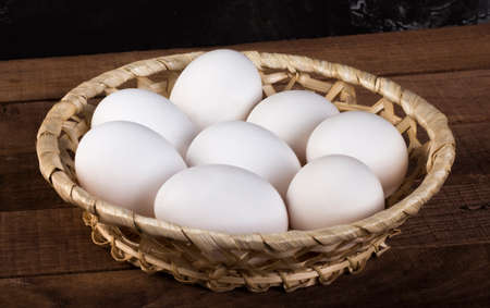 wicker plate with white eggs on a wooden brown background 免版税图像