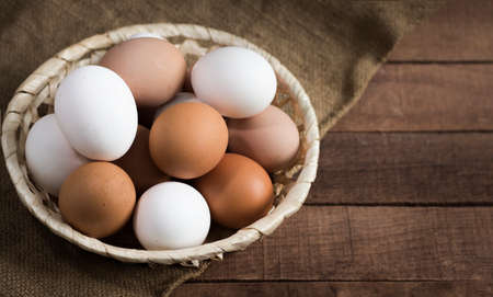 wicker wooden plate with brown and white eggs on a brown wooden background with burlap