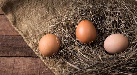 three eggs in a nest of hay on a background of burlap on a wooden surface, top view