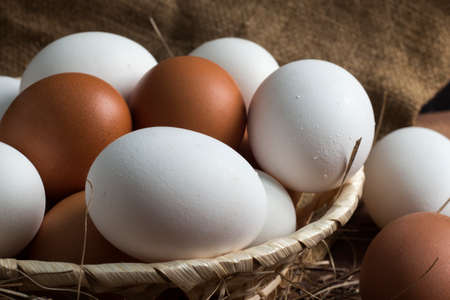wicker wooden plate with brown and white eggs on a background of burlap 免版税图像