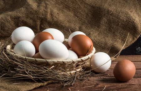 wicker wooden plate, in hay with brown and white eggs on a brown wooden background with burlap 免版税图像