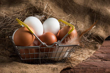 iron food basket with brown and white eggs on a brown wooden background with burlap