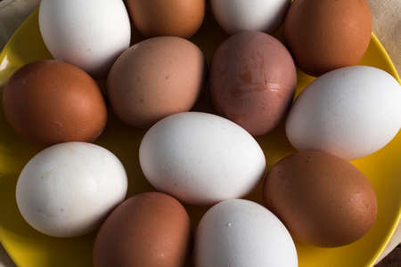 yellow plate with eggs of different colors, close-up view from above