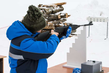 a woman shoots a rifle at a target in the winter in an open area 免版税图像