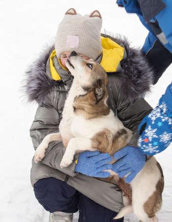 A child lovingly hugs a dog in winter on the street 免版税图像