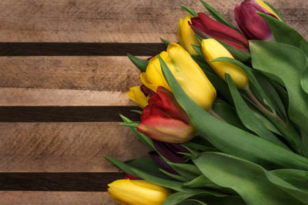 Colorful bouquet of tulips on a wooden background 免版税图像