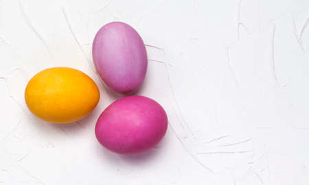Easter bright eggs lay flat on a white textured background with a copy of the space. 免版税图像