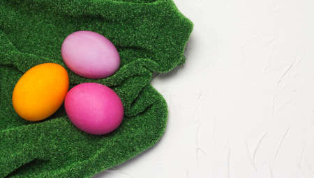 three Easter eggs lay flat on a grass-green tablecloth on a white textured background with a copy of the space