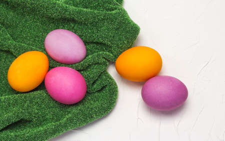 Easter eggs lay flat on a grass green cloth on a white textured background with a copy of the space 免版税图像