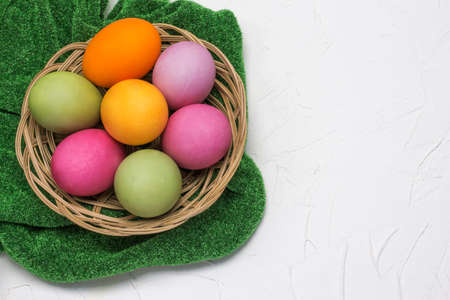 The Easter eggs in the basket flat lay on a grass-green tablecloth on a white textured background with a copy of the space