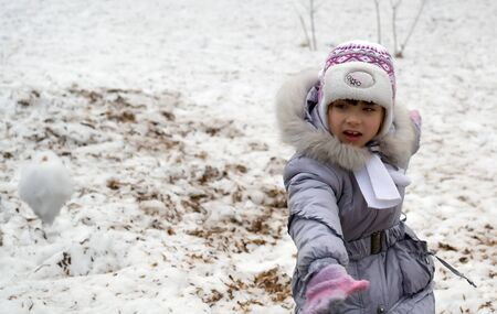 boule de neige: Jeune fille jette boule de neige en hiver