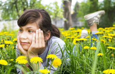 Young girl lies on the lawn with dandelions Banco de Imagens